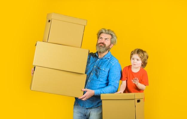Gelukkig zoontje en vader met kartonnen doos verpakking dingen levering en familie tijd concept zoon