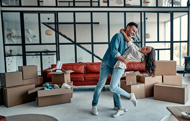 Gelukkig zorgeloos kaukasisch paar eerste keer huizenkopers huurders eigenaren dansen lachend in de woonkamer met dozen samen, grappige huurders plezier genieten van verhuizing in nieuw huis op verhuisdag.