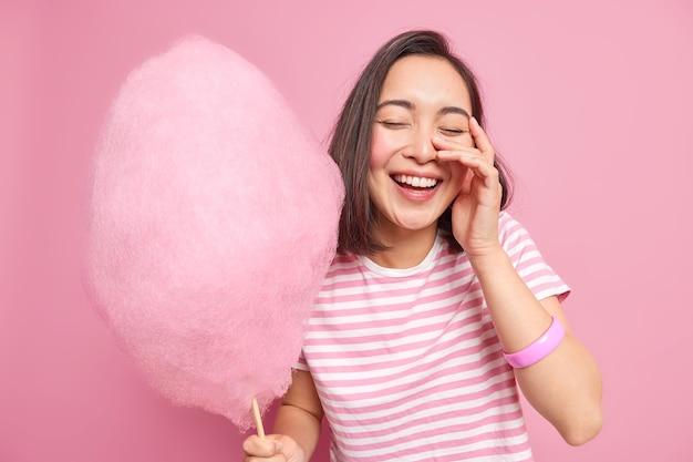 Gelukkig zorgeloze brunette jonge aziatische vrouw heeft plezier houdt ogen gesloten houdt roze suikerspin geniet van vrije tijd met vrienden gekleed in casual gestreept t-shirt eet lekkere dessert poses binnen