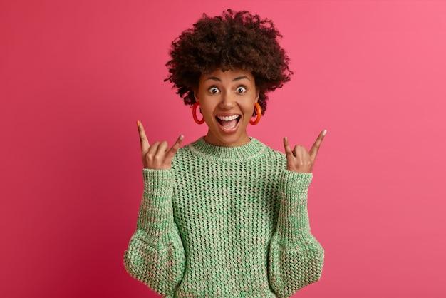 Gelukkig zorgeloze donkere huid rebelse jonge vrouw geniet van geweldige muziek, maakt rock-'n-roll-gebaar, heeft plezier op een muziekfestival of cool evenement, draagt een casual trui, poseert tegen een roze muur.