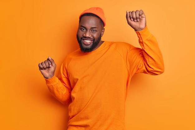 Gelukkig zorgeloze man danst over oranje muur werpt handen beweegt actief glimlacht graag stijlvolle hoed draagt en trui viert succes