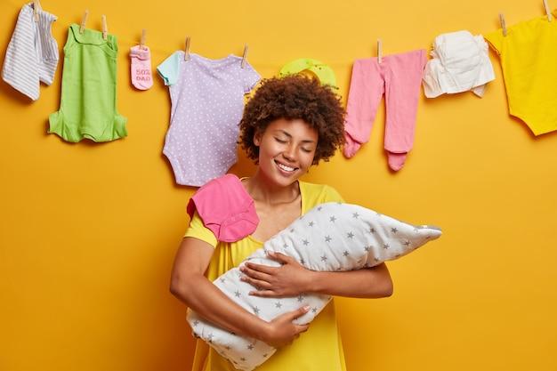 Gelukkig zorgzame moeder en haar baby omhelst teder kind gewikkeld in een deken met grote liefde, zogende geliefde pasgeborene, aanhankelijke mama, geïsoleerd op gele muur, toont bescherming