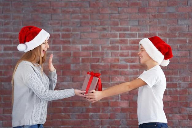 Gelukkig zus en broer met geschenkdoos op bakstenen muur achtergrond