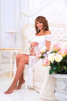 Gelukkig zwanger meisje in een witte kanten jurk zittend op een bed in de buurt van rozen