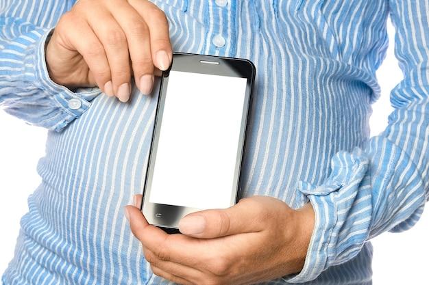 Gelukkig zwanger meisje met een telefoon in haar handen op een witte muur.