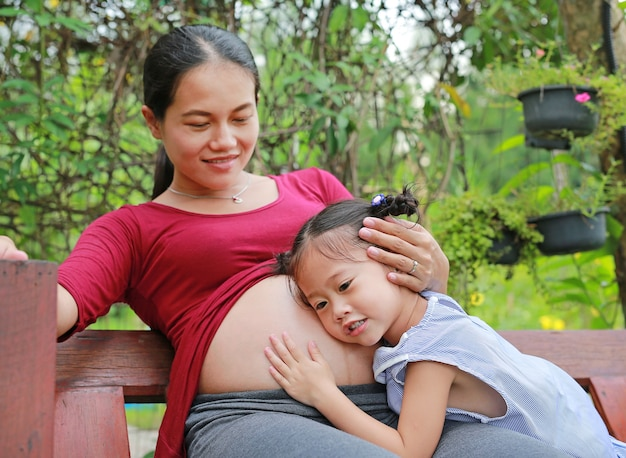 Gelukkig zwanger moeder en meisje die aan zwangere moederbuik luisteren.