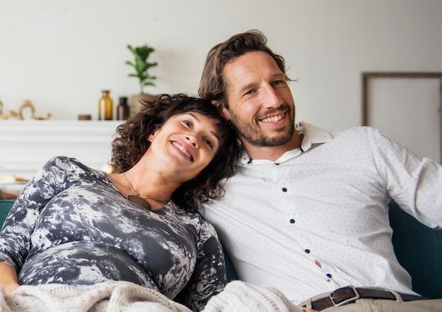 Gelukkig zwanger paar dat op elkaar in de woonkamer leunt