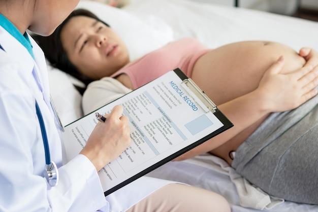 Gelukkig zwangere vrouw bezoek gynaecoloog arts in het ziekenhuis of kliniek voor zwangerschapsconsulent.