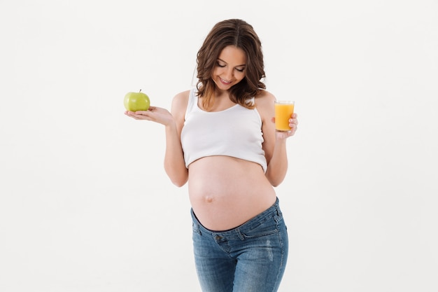 Gelukkig zwangere vrouw het drinken sap. opzij kijken.