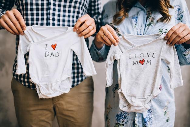 Gelukkig zwangere vrouw huges haar man thuis, stijlvol getrouwd stel, mensen wachten op een kind, mooie zwangere vrouw, gelukkige ouders, liefde in familie