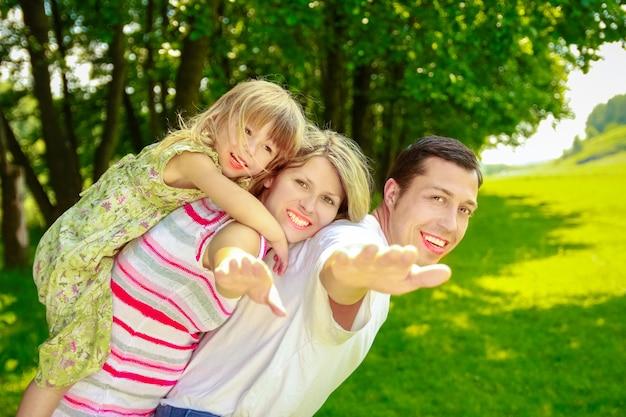 Gelukkig zwangere vrouw met haar familie op de natuur in een park