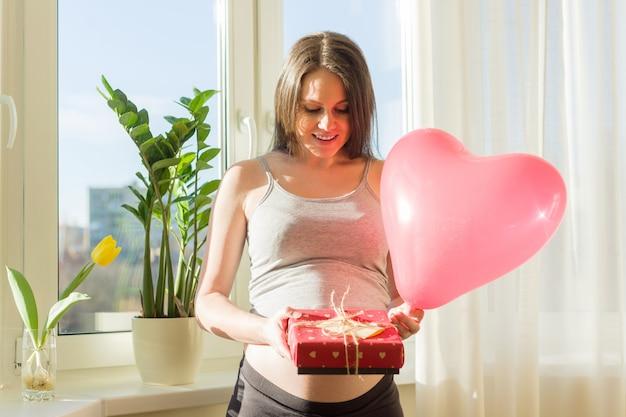 Gelukkig zwangere vrouw met valentines geschenkdoos en rood hart ballon