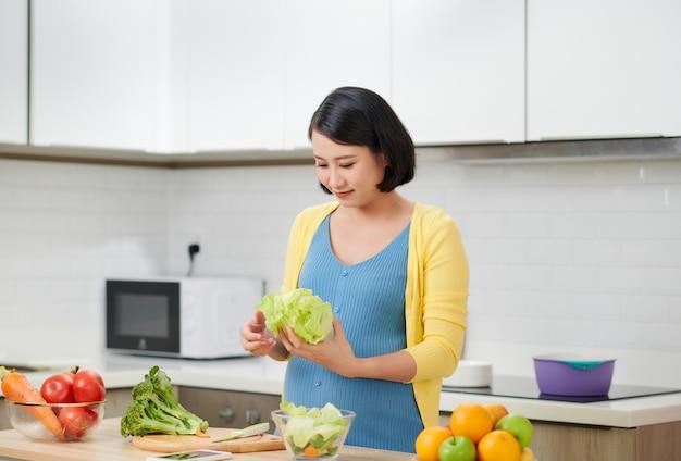 Gelukkig zwangere vrouw thuis koken, verse groene salade doen, veel verschillende groenten eten tijdens de zwangerschap, gezonde zwangerschap concept