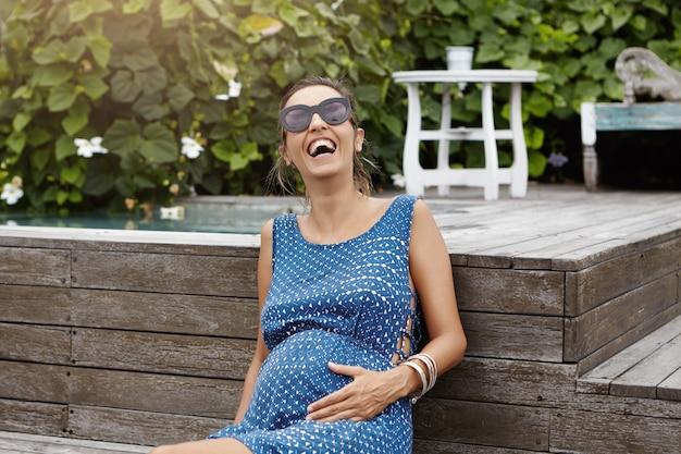 Gelukkig zwangerschap en moederschap concept. jong zwanger wijfje die buiten van zonnebril genieten die van verse lucht en warm weer genieten, bij zwembad op houten vloer zitten en vrolijk lachen