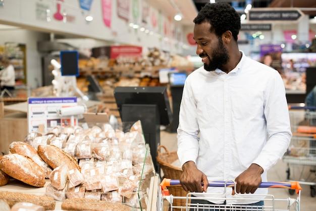 Gelukkig zwart mannetje die brood kiezen bij kruidenierswinkelopslag