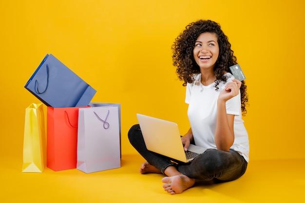 Gelukkig zwart meisje die met kleurrijke die het winkelen zakken met laptop en creditcard zitten over geel wordt geïsoleerd