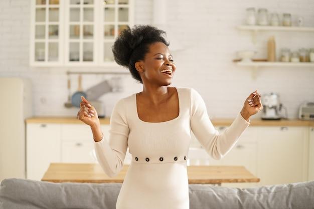 Gelukkig zwart meisje draagt mode jurk dansen genieten van het luisteren naar muziek, plezier alleen thuis.