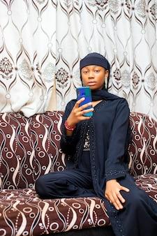 Gelukkig zwart moslimtienermeisje met smartphone-app die geniet van online virtueel chat-videogesprek met vrienden op afstand mobiele chat virtuele vergadering, verhalen opnemen voor sociale media thuis.