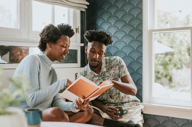 Gelukkig zwart paar dat thuis een boek leest Premium Foto