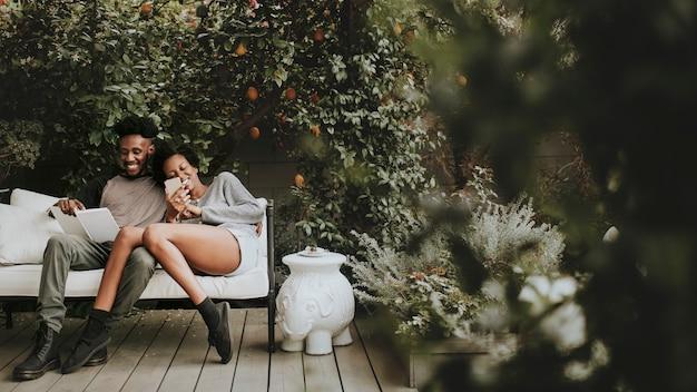 Gelukkig zwart paar genieten in de tuin met een boek en een smartphone