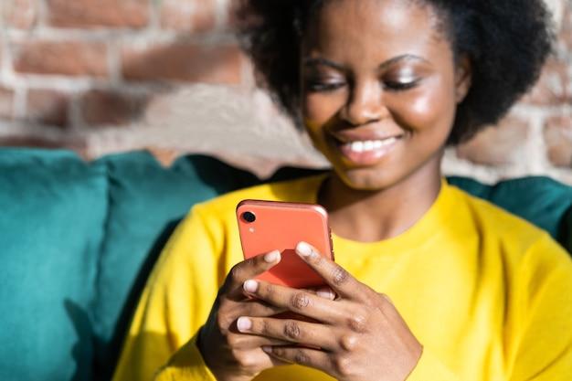 Gelukkig zwarte duizendjarige jonge vrouw met behulp van mobiele telefoon, bericht typen, sociale netwerken opnemen