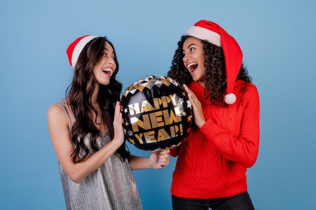 Gelukkig zwarte en kaukasische dame met gelukkige nieuwe jaarballon en kerstmishoeden die over blauw worden geïsoleerd