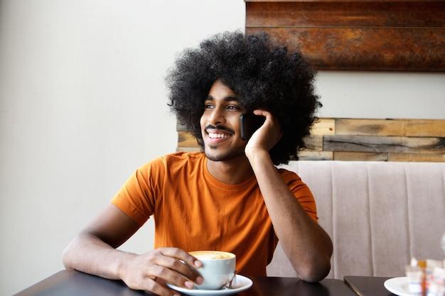 Gelukkig zwarte man zit koffie en mobiele telefoon