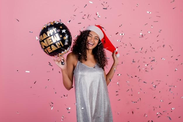 Gelukkig zwarte met gelukkige nieuwe jaarballon en confettien die in de lucht vliegen die over roze wordt geïsoleerd