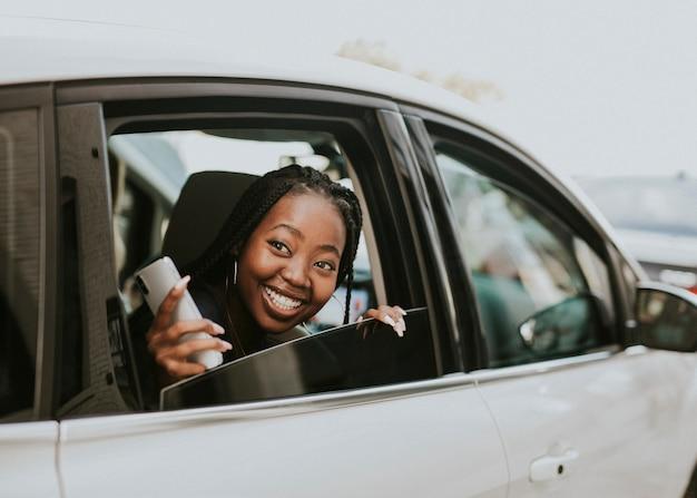 Gelukkig zwarte vrouw kijkt uit de auto het raam