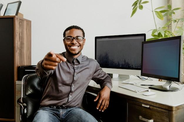 Gelukkig zwarte zakenman wijzend op het scherm