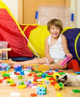 Gelukkige 4 jaar kind spelen met speelgoed