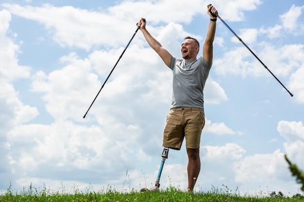 Gelukkige aangename man die zijn handen omhoog houdt terwijl hij geniet van nordic walking-stokken