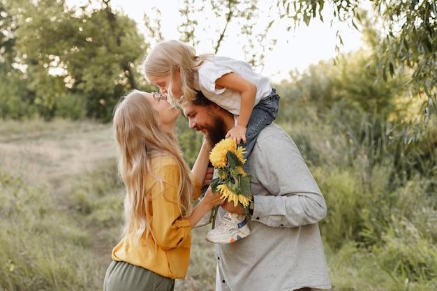 Gelukkige aantrekkelijke familie op een wandeling. dochter in de armen van haar vader kust haar moeder