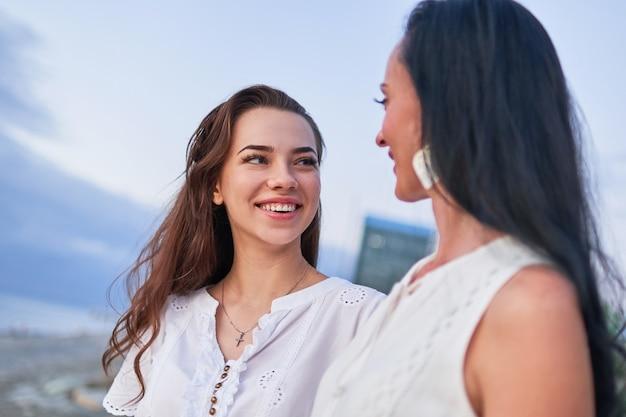 Gelukkige aantrekkelijke glimlachende dochter en moeder die elkaar bekijken en samen plezier hebben