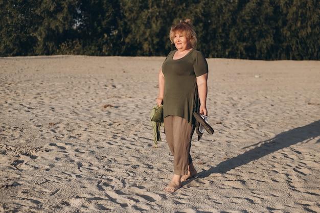 Gelukkige aantrekkelijke hogere vrouw die op zand in de zomer loopt