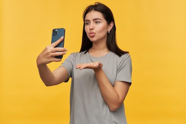 Gelukkige aantrekkelijke jonge vrouw met donker haar in grijze t-shirt die een kus verzendt die eendgezicht maakt en selfie neemt met behulp van mobiele telefoon over gele muur