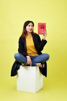 Gelukkige aantrekkelijke jonge vrouwenzitting op lege lege doos die rode giftdoos op gele ruimte houdt