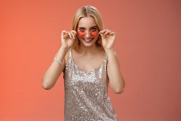 Gelukkige aantrekkelijke stijlvolle europese blonde vrouw met leuke vrienden nachtclub dragen zilveren glinsterende jurk zonnebril kijken geamuseerd nieuwsgierig gluren camera geïntrigeerd, staande rode achtergrond.
