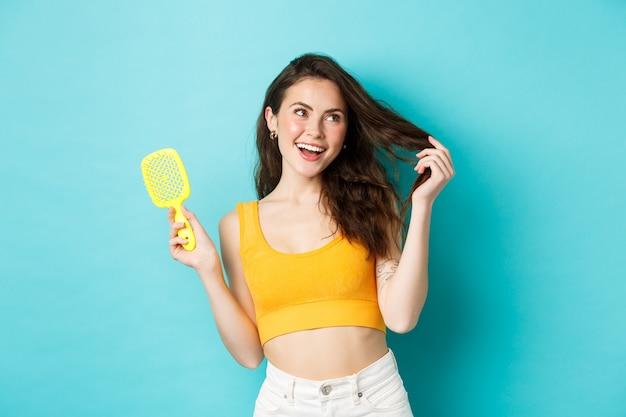 Gelukkige aantrekkelijke vrouw die haar borstel zonder haarstreng laat zien en een gezond lang kapsel aanraakt met een blij gezicht, glimlachend blij met het shampooresultaat, blauwe achtergrond.
