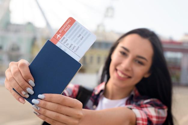 Gelukkige aantrekkelijke vrouw die paspoort en luchtkaartje in openlucht tonen bij