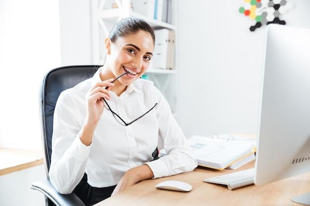 Gelukkige aantrekkelijke zakenvrouw die een bril vasthoudt en op kantoor zit