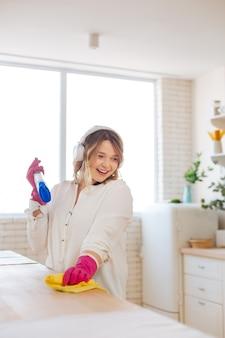 Gelukkige aardige vrouw die de tafel afveegt terwijl ze haar huis schoonmaakt