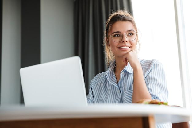 Gelukkige aardige vrouw in bril die met laptop werkt en glimlacht terwijl ze aan tafel in de woonkamer zit