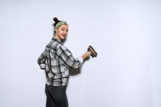 Gelukkige actieve jonge meisjesschilder schildert muren in haar appartement, repareert