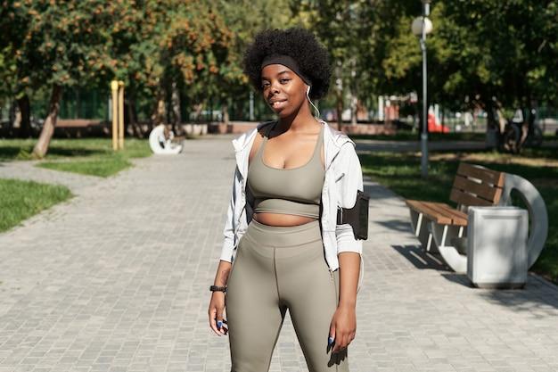 Gelukkige actieve vrouw in sportkleding die naar je kijkt in het park