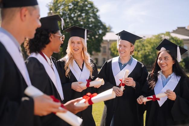 Gelukkige afgestudeerden die afstudeerjurken dragen die buiten staan en praten over hun toekomstplannen