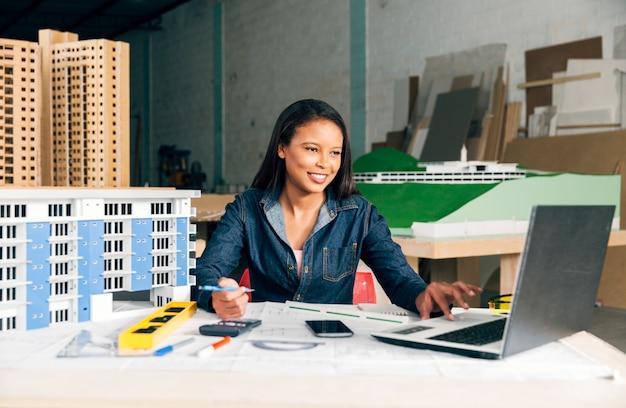 Gelukkige afrikaans-amerikaanse dame met laptop en model van de bouw aan tafel