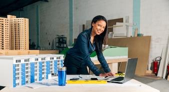 Gelukkige Afrikaans-Amerikaanse dame met laptop en model van het voortbouwen op lijst