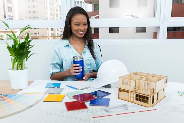 Gelukkige afrikaans-amerikaanse dame op stoel met vacuümbeker dichtbij plan en model van huis op lijst