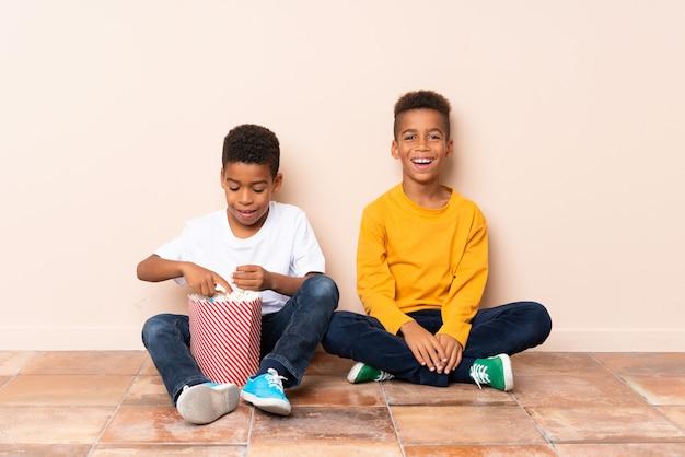 Gelukkige afrikaanse amerikaanse broers die popcorns houden